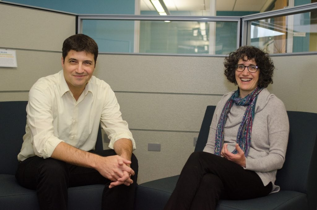 Man and woman sitting in office cubicle talking
