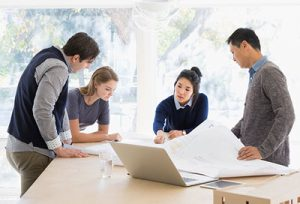 a group of young professionals gathered around a table looking at documents