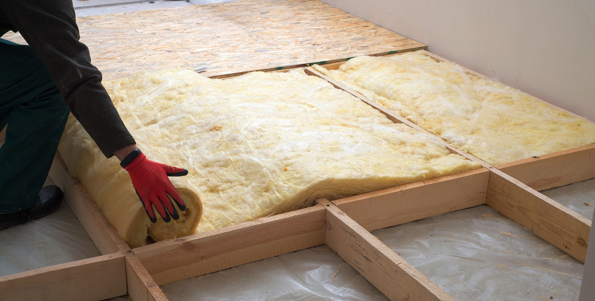 Work composed of mineral wool insulation in the floor, floor heating insulation , warm house, eco-friendly insulation, a builder at work