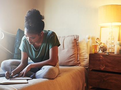 Woman writing and sitting on couch