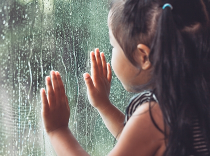 child looking at rain through window